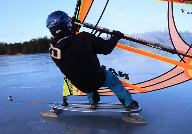 Tobias Bodin on a lake near Stockholm, Sweden, riding his iceboard with a cambered sail. He's wearing a motorbike helmet for safety, go pro camera at the front of the board.